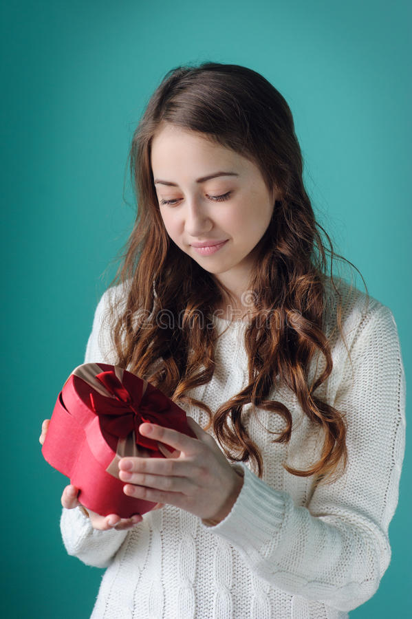 Beautiful woman considering a gift in the form of heart on Valentine's Day stock image