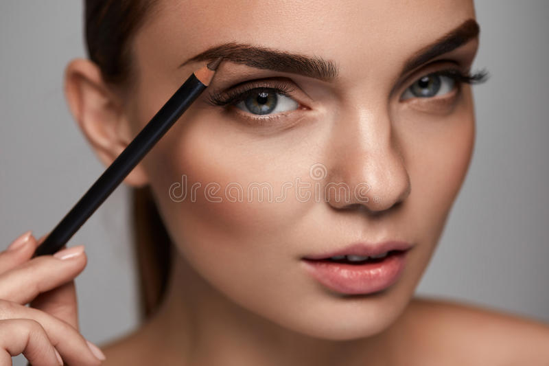 Beautiful Woman Contouring Eyebrows With Pencil. Beauty royalty free stock image