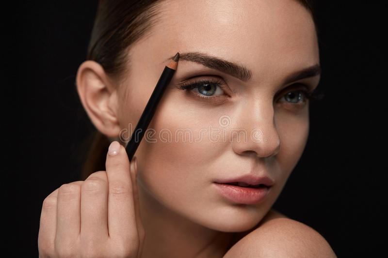 Beautiful Woman Contouring Eyebrows With Pencil. Beauty stock photo