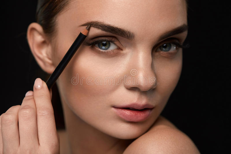 Beautiful Woman Contouring Eyebrows With Pencil. Beauty royalty free stock photography