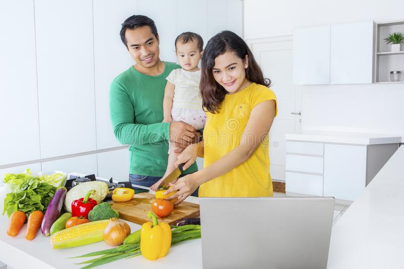 Beautiful woman cooks with her baby and husband royalty free stock photography