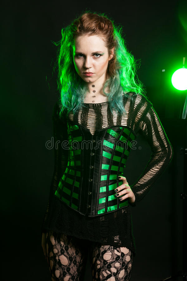 Beautiful Woman in cosplay corset posing in studio. With a green light from behind. Studio photo. Fashion and cosplay stock image