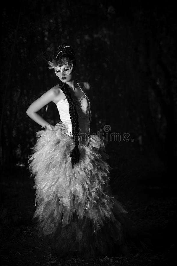 Beautiful woman in couture dress standing in a forest. Monochrome image of a beautiful young Caucasian woman wearing her long dark hair in an elaborate braided royalty free stock photo
