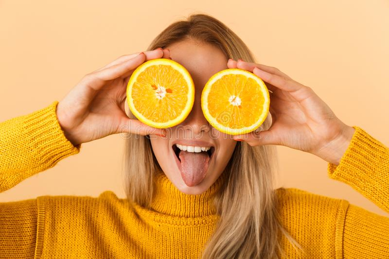 Beautiful woman covering eyes with citrus lemons posing isolated over yellow wall background royalty free stock photography