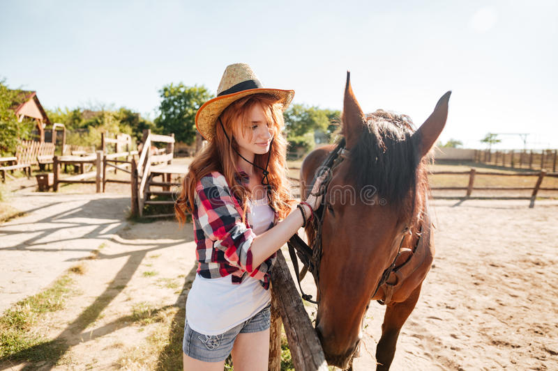 Beautiful woman cowgirl taking care of her horse on farm stock photo