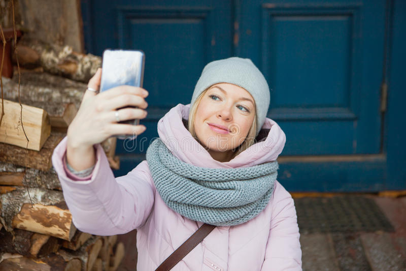 Beautiful woman in cozy scarf make selfie on porch outside. Young lady smile looking at mobile smartphone stock image