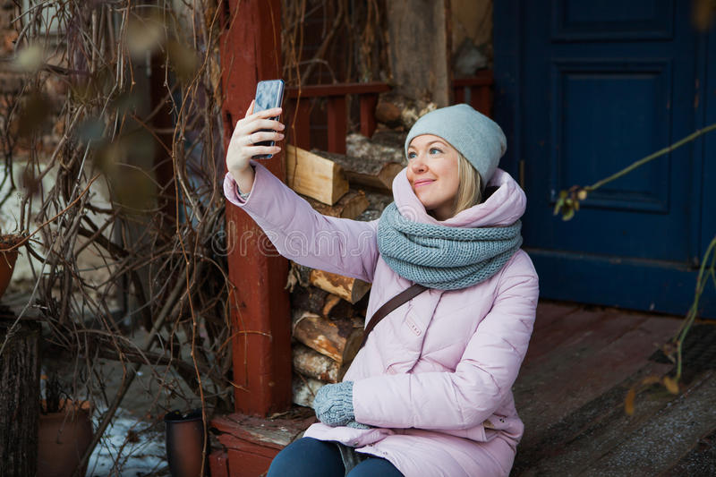 Beautiful woman in cozy scarf make selfie on porch outside. Young lady smile looking at mobile smartphone royalty free stock photos