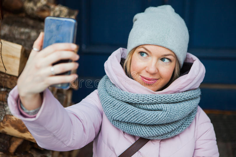 Beautiful woman in cozy scarf make selfie on porch outside. Young lady smile looking at mobile smartphone royalty free stock photo