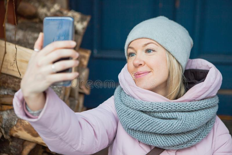 Beautiful woman in cozy scarf make selfie on porch outside. Young lady smile looking at mobile smartphone stock images