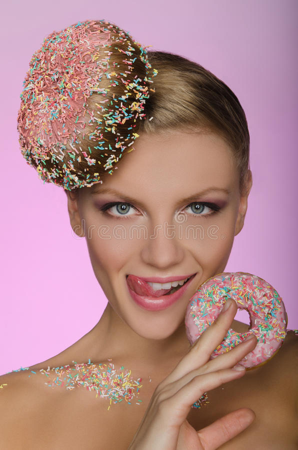Beautiful woman with creative hairstyle from donut. On pink background stock photo