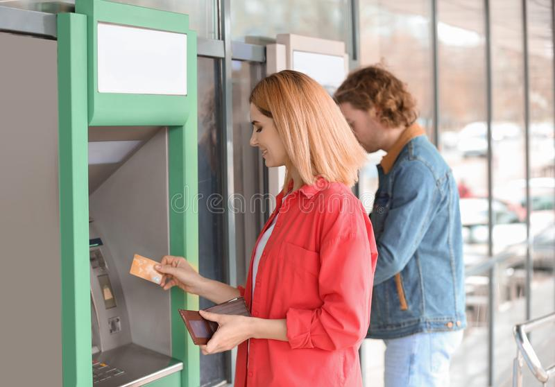 Beautiful woman with credit card near cash machine royalty free stock images