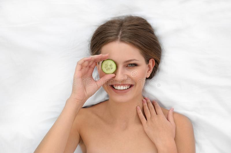 Beautiful woman with cucumber slice on white fabric. Organic face mask. Beautiful woman with cucumber slice on white fabric, above view. Organic face mask stock photos