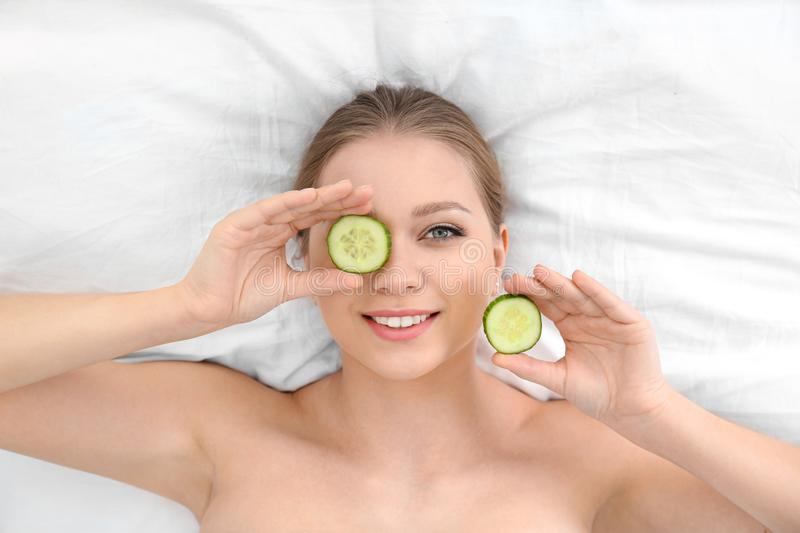 Beautiful woman with cucumber slices on white fabric. Organic face mask. Beautiful woman with cucumber slices on white fabric, above view. Organic face mask royalty free stock photos