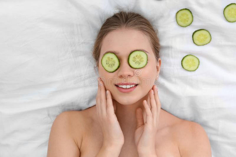 Beautiful woman with cucumber slices on white fabric. Organic face mask. Beautiful woman with cucumber slices on white fabric, above view. Organic face mask stock image