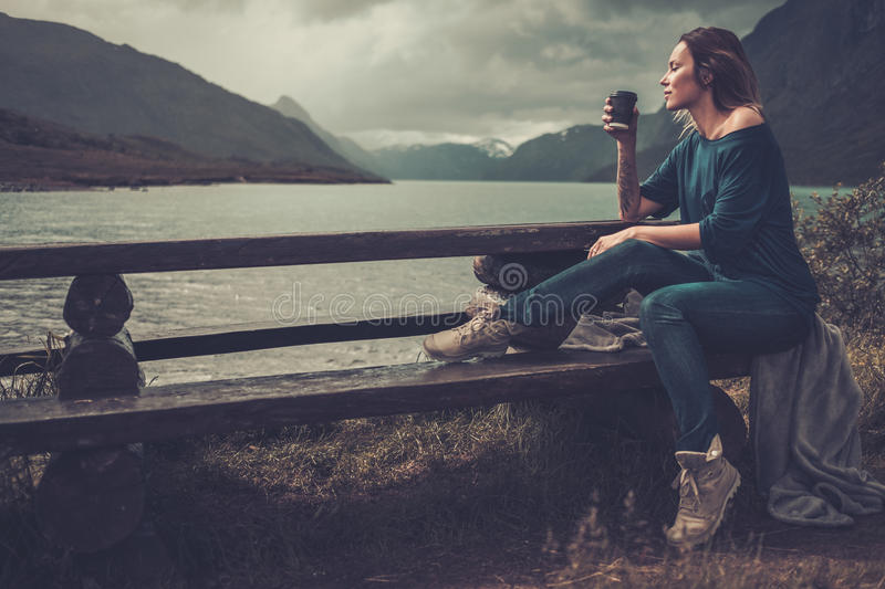 Beautiful woman with cup of coffee or tea sitting on a banch near the wild lake, with mountains on the background. stock image