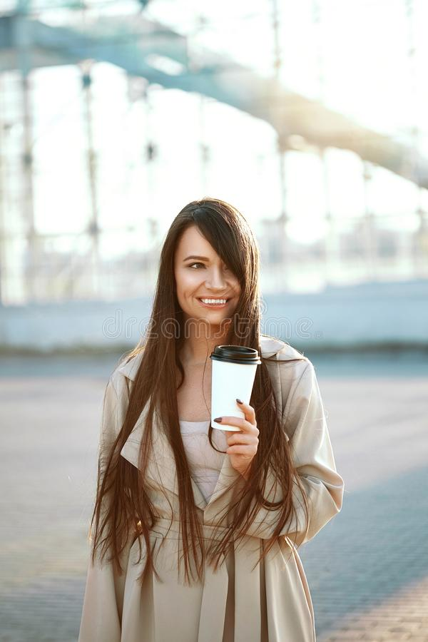 Beautiful Woman With Cup Of Coffee Walking On Street. Portrait Of Attractive Young Female In Stylish Office Clothes Holding Cup Of royalty free stock photo