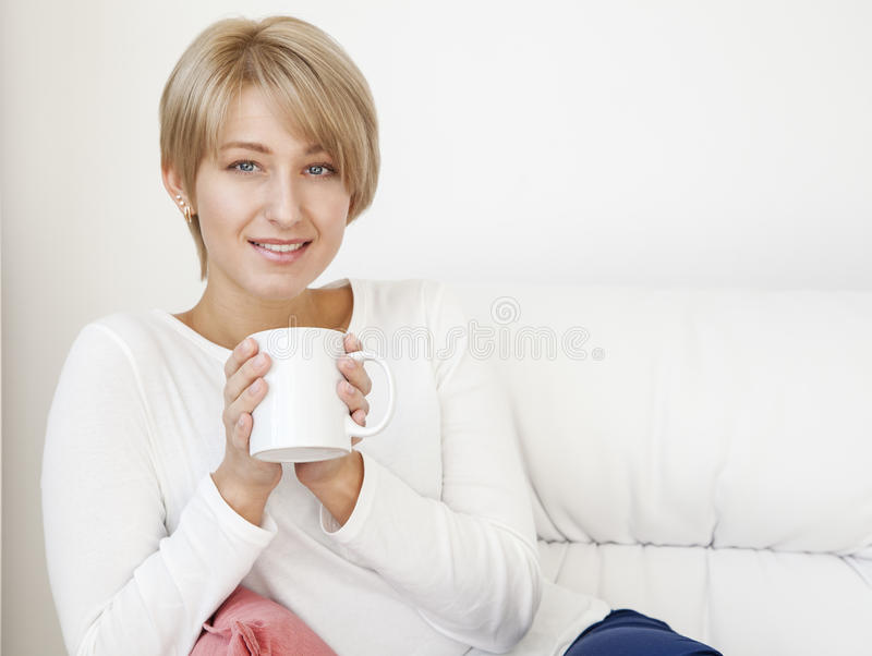Beautiful woman with a cup on a white couch stock photos