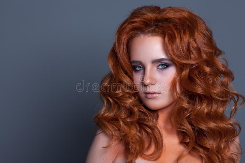 Beautiful woman with curls in hair of red color and creative make-up royalty free stock image