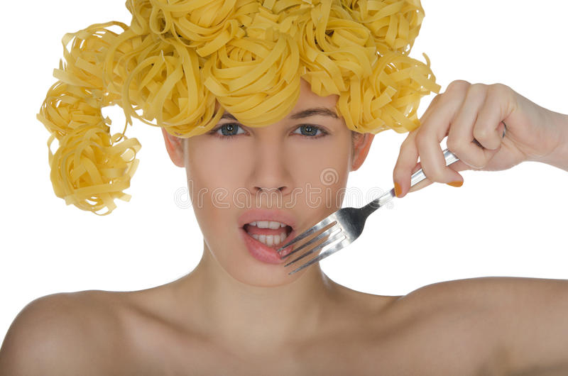 Beautiful woman with curls of pasta biting fork. Beautiful young woman with curls of pasta biting fork royalty free stock photos