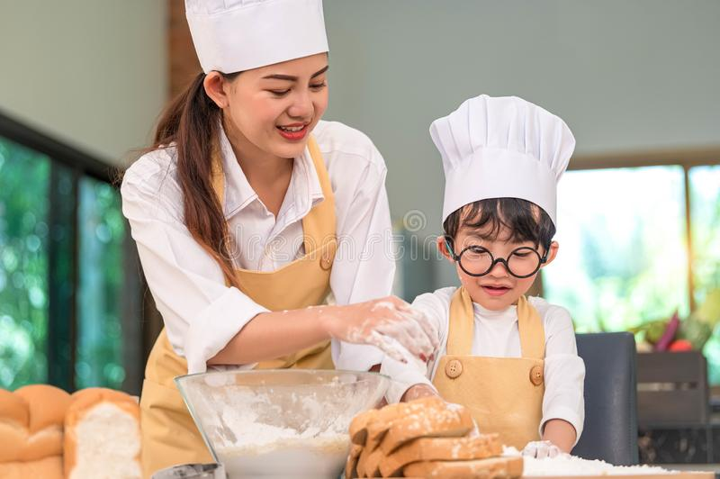 Beautiful woman and cute little Asian boy with eyeglasses, chef hat and apron playing and baking bakery in home kitchen funny. stock images