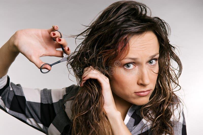 Beautiful woman cutting her hair stock photography