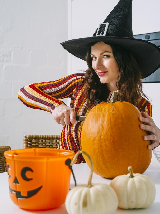 Beautiful woman cutting a pumpkin for Halloween royalty free stock photography
