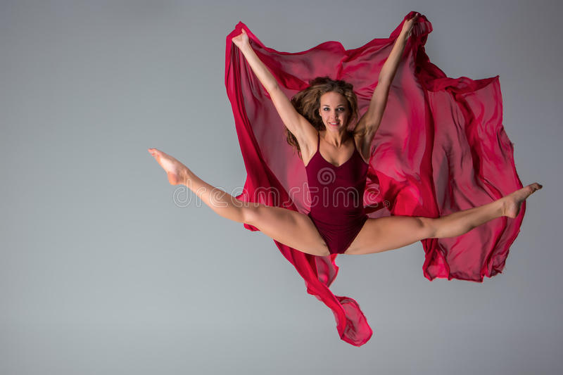 Beautiful woman dancer wearing maroon swimsuit posing on a grey studio background. Young beautiful woman dancer with long brown hair wearing maroon swimsuit royalty free stock images