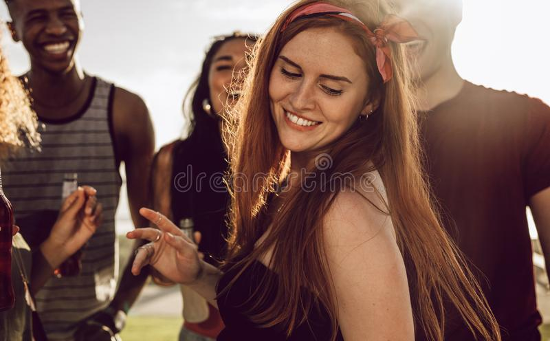 Beautiful woman dancing with friends. Beautiful women dancing with friends around outdoors. Woman having a great time with group of friends on summer day stock image