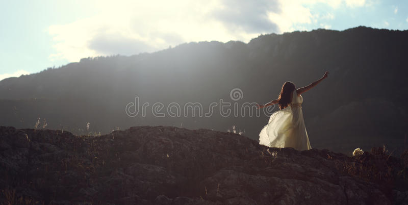 Beautiful woman dancing in sunset light. Young beautiful woman bride in long white dress stretching arms and dancing on mountain stock photo