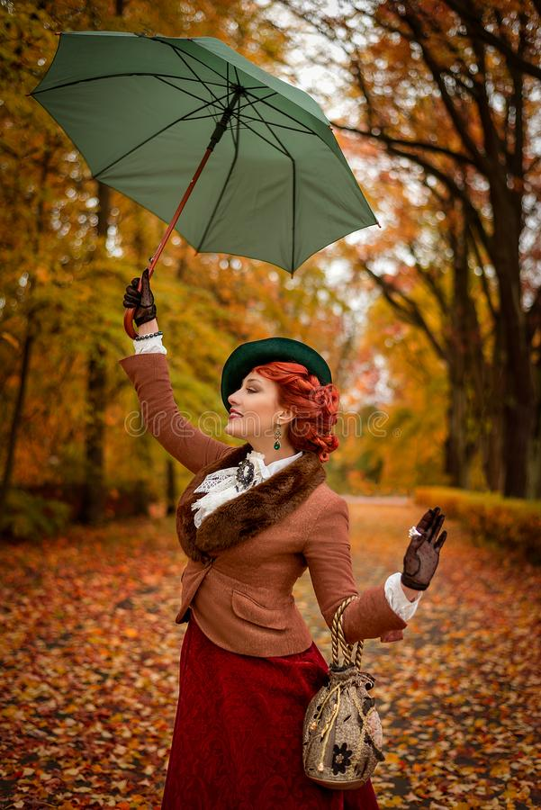 Beautiful woman dancing with umbrella in the park stock images