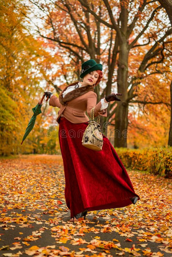 Beautiful woman dancing with umbrella in the park royalty free stock photo