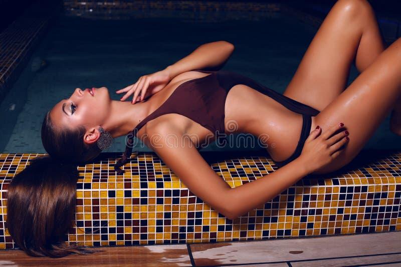 Beautiful woman with dark hair in bikini posing in night swimming pool stock photography