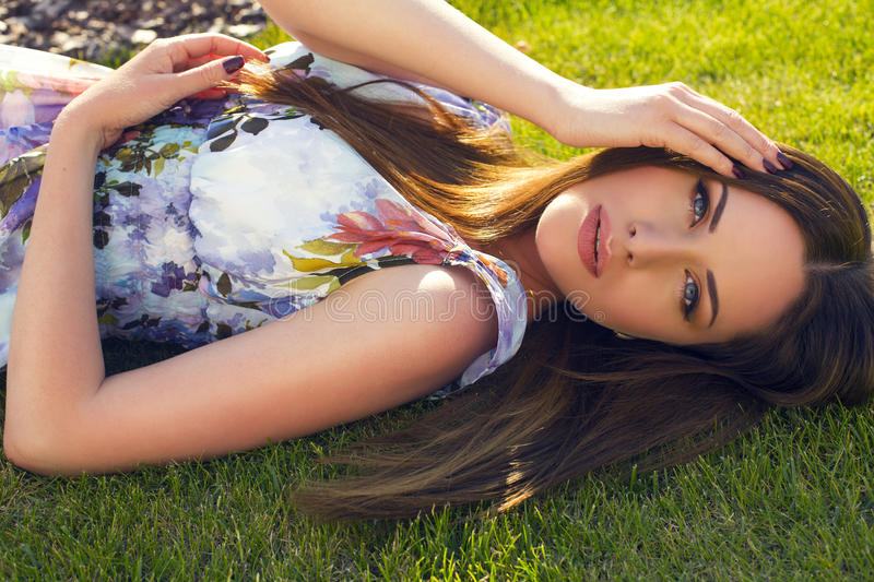 Beautiful woman with dark hair and blue eyes at garden. Beautiful woman with dark hair and blue eyes relaxing at summer garden stock photography