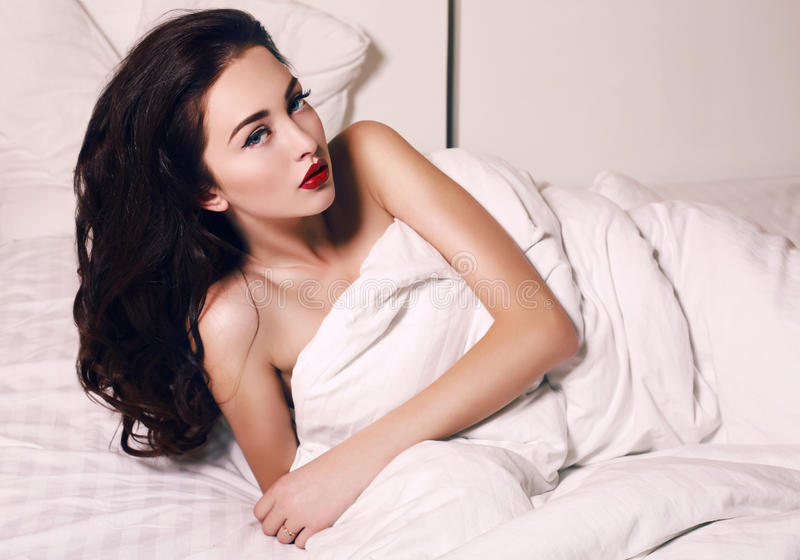 Beautiful woman with dark hair and blue eyes lying in bed royalty free stock image