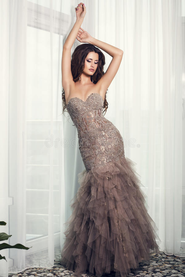 Beautiful woman with dark hair in luxurious dress posing at bedroom royalty free stock photos