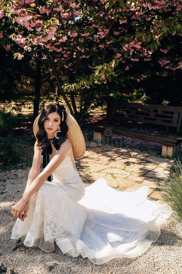 Beautiful woman with dark hair in luxurious wedding dresses with accessories posing in garden with blossoming sakura trees. Fashion outdoor photo of beautiful royalty free stock image