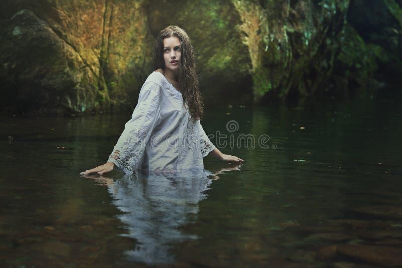 Beautiful woman in a dark magical stream royalty free stock photo