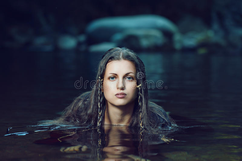 Beautiful woman in dark water stream royalty free stock images