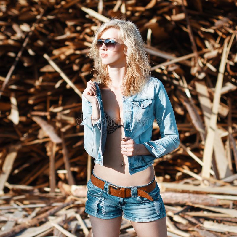 Beautiful woman in denim jeans shorts and jacket. Standing on th royalty free stock images