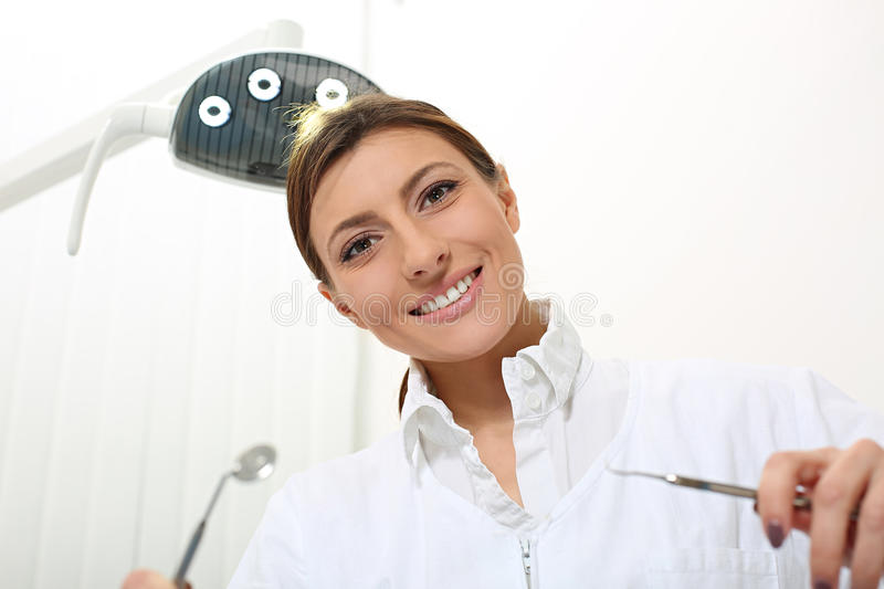 Beautiful woman dentist ready to examine the patient. With dental probe and mirror royalty free stock photos