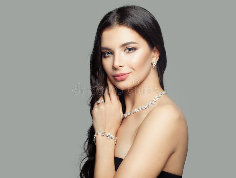 Beautiful woman with diamond ring, necklace, bracelet and earrings. Cute smiling girl.  stock images