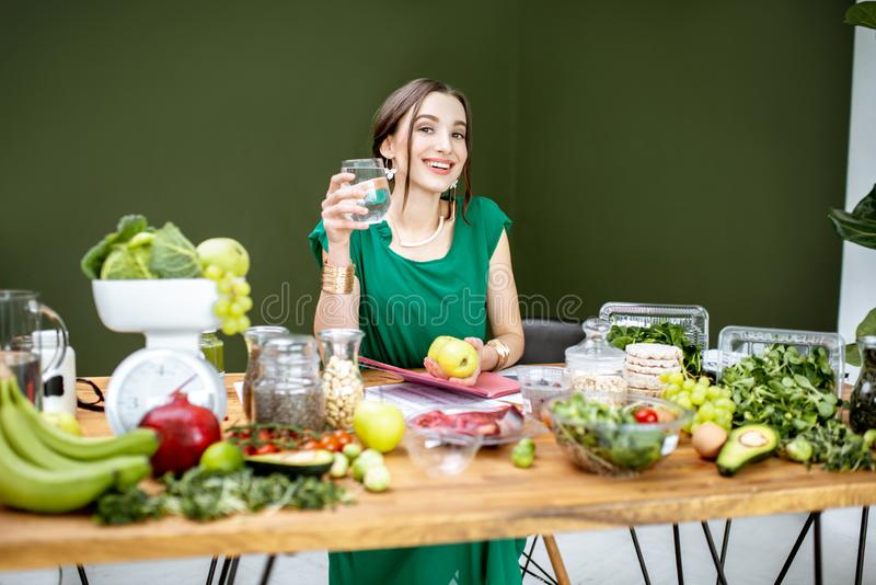 Beautiful woman dietitian with healthy food. Portrait of a beautiful woman as a dietitian sitting with glass of water and various healthy food ingredients in the royalty free stock photo