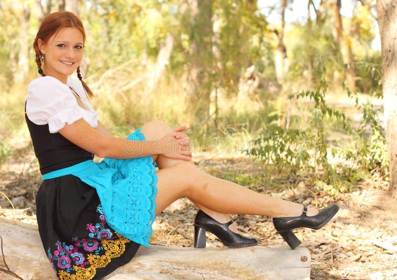 Beautiful Woman in Dirndl Posing on Fallen Tree stock photos