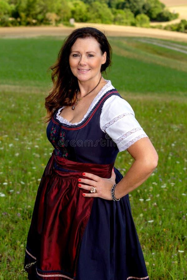Beautiful woman in dirndl standing in meadow royalty free stock image
