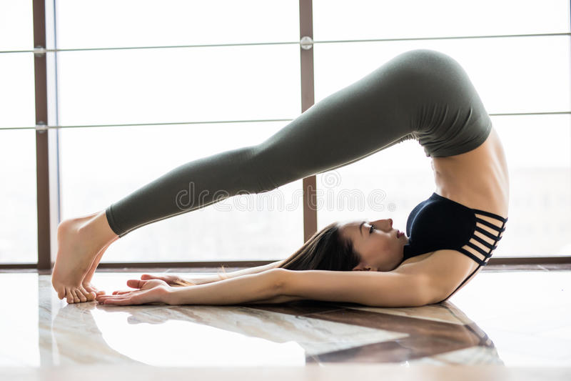 Beautiful woman do yoga exercises halasana against window in studio stock images