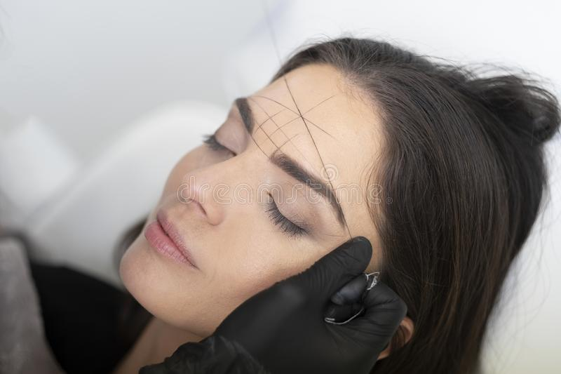 Beautiful woman is doing her eyebrows in the beautician. royalty free stock photo