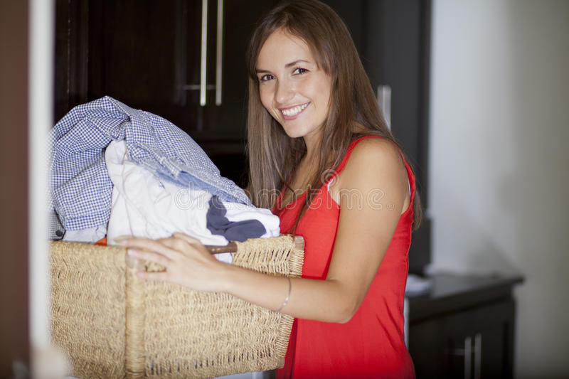 Beautiful woman doing laundry. Cute young housewife loading the washer with clothes stock images