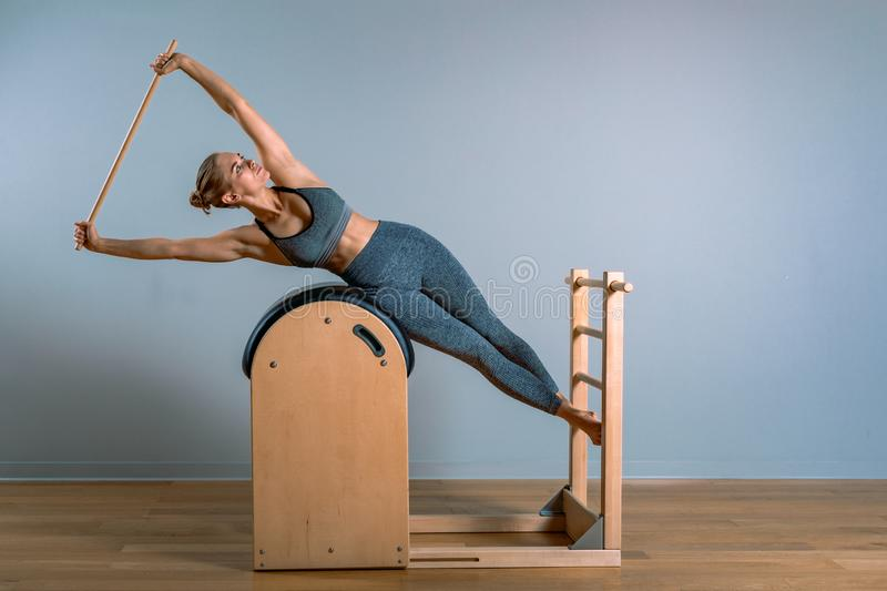 Beautiful woman doing pilates exercise, training on barrels. Fitness concept, special fitness equipment, healthy. Lifestyle, plastic. Copy space, sport banner royalty free stock images