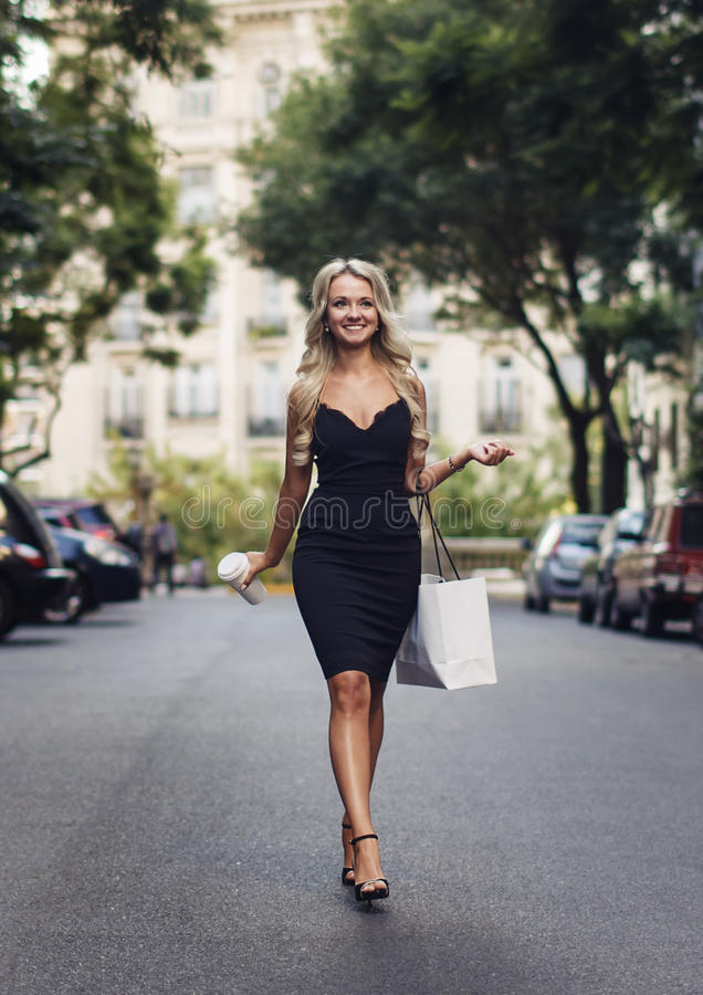 Beautiful woman doing shopping going to her car in the parking royalty free stock photo