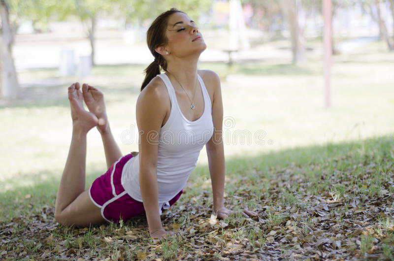 Beautiful woman doing yoga. Cute young woman doing some yoga at the park stock photo